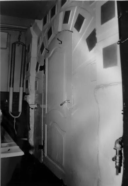 Wejście doczarnej kuchni zboniowaną dekoracją ściany. Widoczne miejsca poflizach.