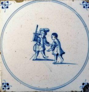 Aktor zteatrzykiem kukiełkowymna plcach idziecko, przedstawienie wpisane wpodwójny medalion, ornament narożnikowy typu pająk, Amstardam Ip. XVIII w.