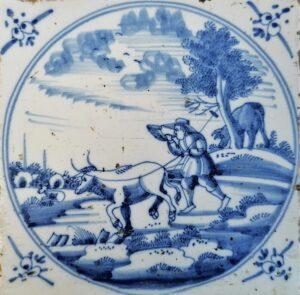 Pejzaż zpasterzem dmącym wróg iprowadzącym byka, przedstawienie wpisane wpodwójny medalion, ornament narożnikowy wola główka, Amstardam Ip.XVIII w.